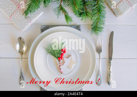 Christmas table setting with traditional Christmas decoration in white red tone. Beautiful  festive dinner background. Xmas tableware, plate with napk
