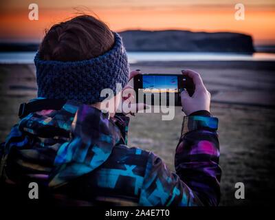 Anonymous unrecognizable traveler shooting sunset on seashore