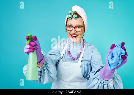 Cleaning Lady Fun. Elderly funny housewife fooling around with a broom. Full body isolated. Comical cleaning lady, old woman funky - Stock Photo