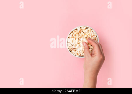 Woman with paper bucket of popcorn. Woman with paper bucket of popcorn. Flat lay style composition, top view. - Stock Photo