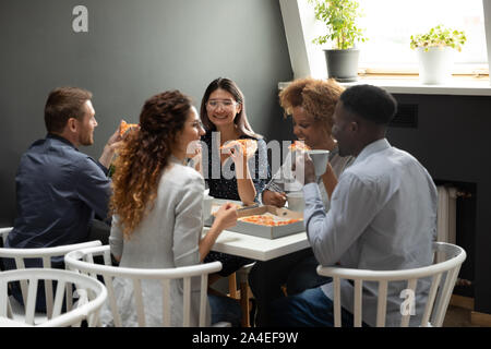 Multi-ethnic friendly colleagues during lunch eating pizza - Stock Photo