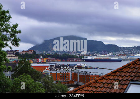 Scenic view of Bergen on a cloudy day. Mountains, fjord, wooden houses with tiled roofs, cruise ships. Hordaland, Norway.