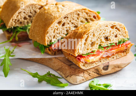 Ciabatta, cheese, ham and vegetable sandwiches on a wooden board. - Stock Photo