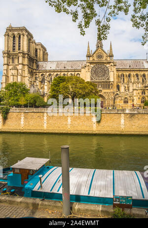 barge on river seine with notre dame cathedral in background - Stock Photo