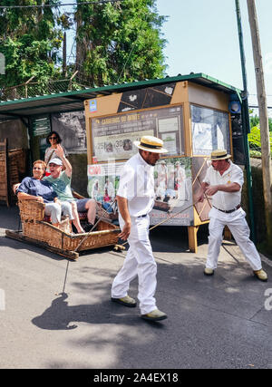 Monte, Madeira, Portugal - Sep 14, 2019: Wicker Basket Sledges drivers, Carreiros do Monte, driving people downhill. Historical mean of transport, now a tourist attraction. Typical straw hat. - Stock Photo