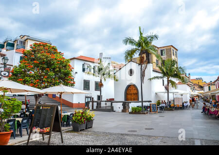 Funchal, Madeira, Portugal - Sep 10, 2019: Street in Madeiran capital with typical restaurants and cafes. People drinking and eating on outdoor terraces. Colonial architecture. Historical center. - Stock Photo