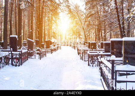 Winter cemetery in the background of the sun, alley. Copy space, graveyard - Stock Photo