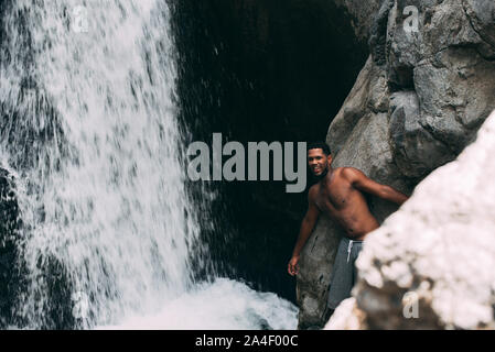 black man shirtless under a waterfall cascade in rocky river of Africa - Stock Photo