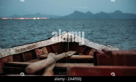 Picturesque view of old fishing boat on sea with mountain city on background at sunset - Stock Photo