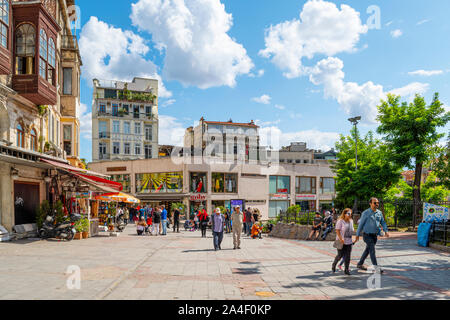 Tourists and local Turks enjoy a summer day in the Karakoy Galata district of shops and cafes in Istanbul, Turkey. - Stock Photo