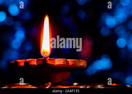 One Glowing earthen lamp on a pile of coins showing influx of money and prosperity - Lakshmi Pooja and Diwali Concept - Stock Photo