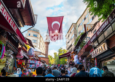 Local Turks enjoy the expansive outdoor market bazaar as they walk under a flying Turkish Flag in Istanbul, Turkey. - Stock Photo