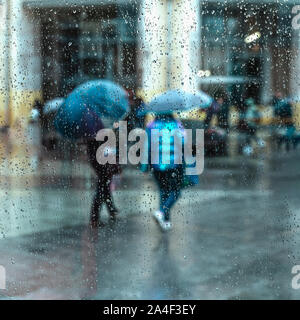 Abstract people under the umbrella, rainy weather, blurred motion. View through glass window with rain drops on glass with street bokeh lights - Stock Photo