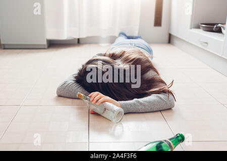 Female alcohol addiction. Young woman sleeping on kitchen floor after party holding bottle - Stock Photo