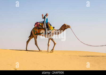 A female tourist on a camel trek waving for a picture atop her camel, the Thar Desert, Rajasthan, India. - Stock Photo