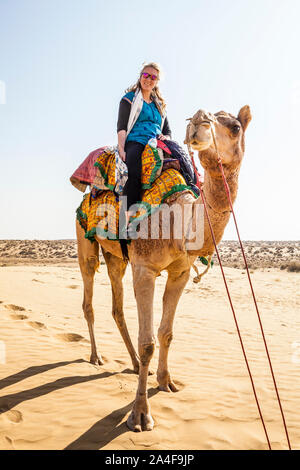 A female tourist on a camel trek sitting atop her camel, the Thar Desert, Rajasthan, India. - Stock Photo