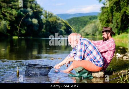 they are ready for the fishing. retired father and mature bearded son. big game fishing. relax on nature. happy fishermen friendship. Two male friends fishing together. fly fish hobby of men. - Stock Photo