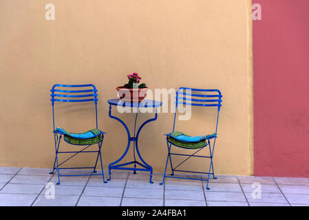 Agios Nikolaus, Crete, Greece. October 2019. Table with two chair and a pot plant on the sidewalk.