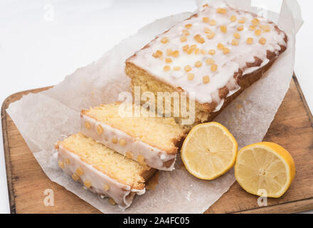 Sliced homemade iced and decorated lemon drizzle cake on a wooden chopping board. - Stock Photo