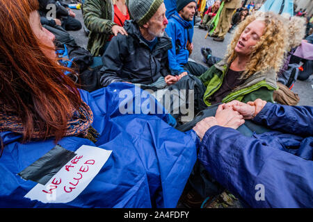 London, UK. 14th Oct, 2019. Glued together since 11 in the morning - Protestors move into the financial centre by blocking the junction at Bank - The sixth day of the Extinction Rebellion October action which has blocked roads in central London. They are again highlighting the climate emergency, with time running out to save the planet from a climate disaster. This is part of the ongoing ER and other protests to demand action by the UK Government on the 'climate crisis'. The action is part of an international co-ordinated protest. Credit: Guy Bell/Alamy Live News - Stock Photo