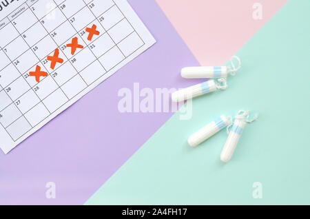 Flat lay composition with calendar and menstrual tampons on blue pink and lilac pastel background. Gynecology concept. Critical days pms period items - Stock Photo
