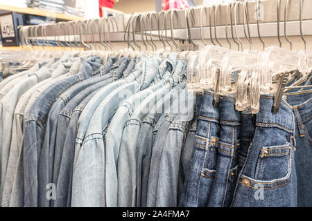 Male mens denim jeans shirts sorted on clothes hangers on a shop wardrobe closet
