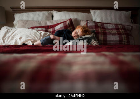 Toddler boy asleep on red plaid bed in pillows at home - Stock Photo