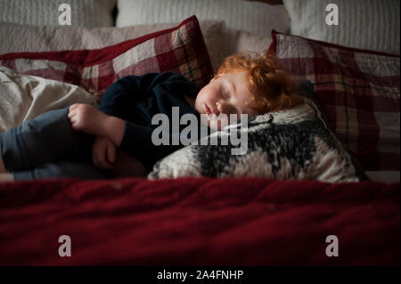 Toddler boy 1-2 years old asleep on pillows in bed with red bedding - Stock Photo