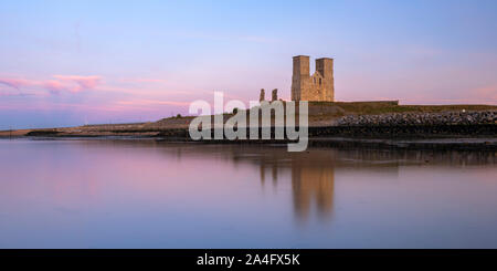 Reculver Towers; a medieval church and site of a Roman fort reflected in the low tide at sunset. - Stock Photo
