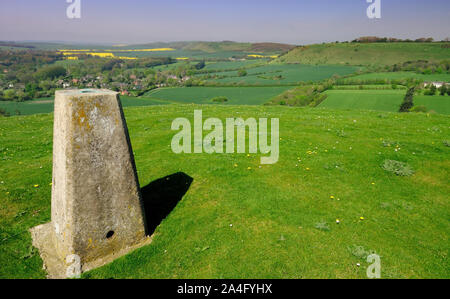 Triangulation pillar beside the Giants Grave (250m) overlooking the village of Oare in the Vale of Pewsey, Wiltshire. - Stock Photo