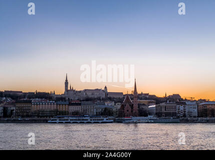 Panorama of Budapest during sunset with river cruise boats docked by the riverside. - Stock Photo