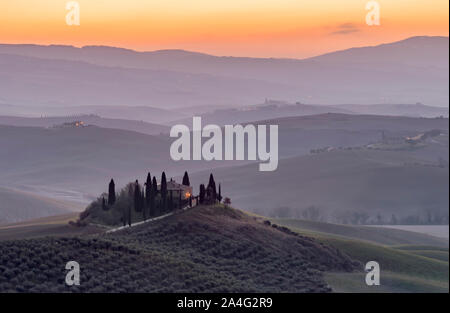The Tuscan countryside in the province of Siena shrouded in morning mist before the dawn of a new day - Stock Photo