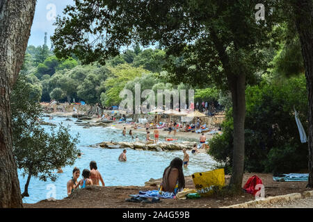 Rovinj, Croatia, August 23: Citizens and tourists sunbathe on the Mulini beach and swim in the clear waters of the Adriatic on a bright sunny day, Aug - Stock Photo