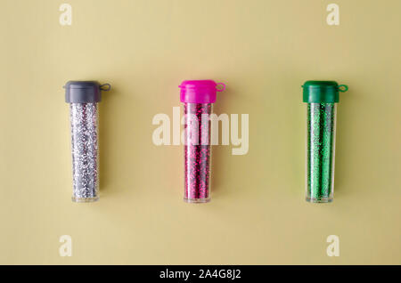 Colorful bottles of glitters on pastel yellow background. Top view. - Stock Photo