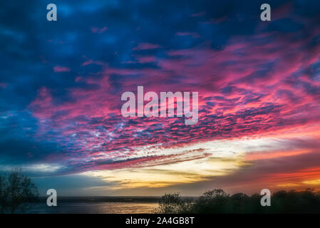 Fabulous, dramatic sky and cloudscape at sunset over Pegwell Bay in Ramsgate, Kent, UK. The colour of the sky is reflecting in the water. - Stock Photo