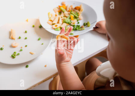 One-year-old baby eats the food from his plate directly with his hands. - Stock Photo