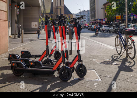 Group of E-scooters from startup company with idea of Eco friendly mobility for urban lifestyle by sharing Electric Scooter, park on shady sidewalk. - Stock Photo