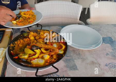 Seafood paella on the table in a seafront restaurant. Risotto, prawns, mussels, clams, squid, fish and peppers in a traditional metal round pot. - Stock Photo