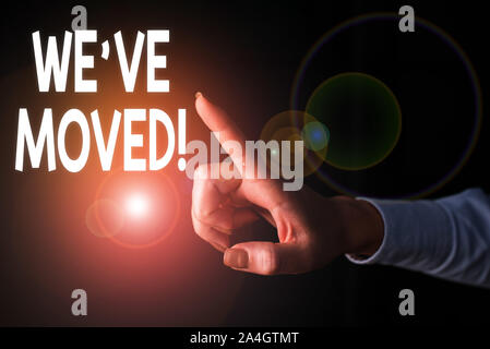 Writing note showing We Ve Moved. Business concept for To go from one residence or location to another Relocate Finger pointing in the Dark with hand - Stock Photo