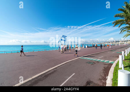Joggers and walkers pass by the Blue Chair balancing along the Promenade des Anglais on the French Riviera in Nice France along the Mediterranean Sea. - Stock Photo