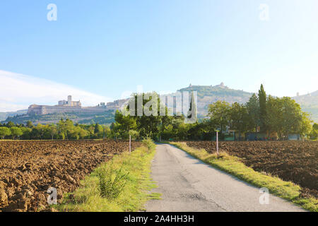 Morning in typical Italian countryside of the heart of Italy with the town of Assisi and Saint Francis Basilica on the background. - Stock Photo
