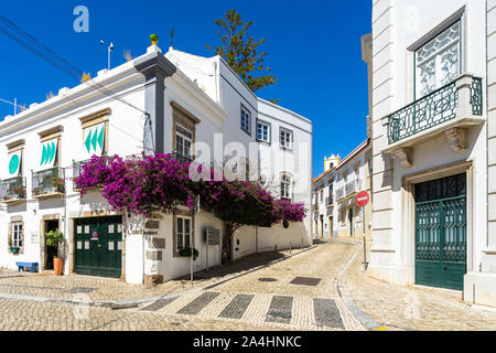 A picturesque street in Tavira with whitewashed houses decorated with bougainvillea flower,  Algarve, Portugal - Stock Photo