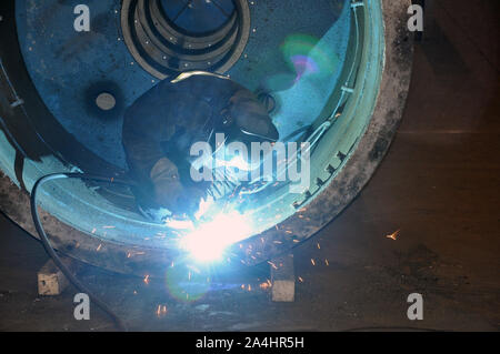 Professional welder welds an industrial tank in a workshop. - Stock Photo