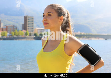 Successful positive female athlete wearing armband blank for advertising before running or exercising outdoor in summer. Woman success in sport lifest - Stock Photo