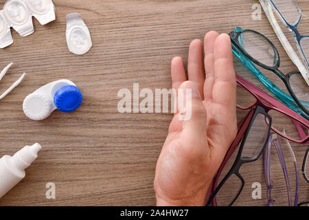 A man's hand rejecting a lot of glasses in favor of contact lenses on wood table. Horizontal composition. Top view. - Stock Photo