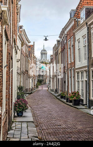 Middelburg, The Netherlands, October 9, 2019: narrow street in the old town, lined with brick houses, with the tower of Oostkerk church in the distanc - Stock Photo