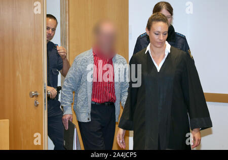 Augsburg, Germany. 15th Oct, 2019. A defendant (M) is led next to his lawyer Martina Sulzberger (r) into a courtroom of the Criminal Justice Centre. The farmer from Northern Swabia has been standing before the Augsburg Regional Court since Tuesday because he is said to have knocked his wife unconscious and then poured liquid manure over her until she suffocated. The man denies the crime. Credit: Karl-Josef Hildenbrand/dpa - ATTENTION: The accused was made unrecognizable on personal rights grounds/dpa/Alamy Live News - Stock Photo