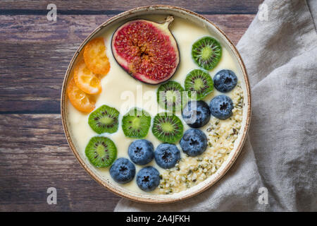 A fresh healthy organic yogurt smoothie bowl seen from above with a variation of fresh fruits - blueberries, mini kiwis, figs, passion fruit and kumqu - Stock Photo