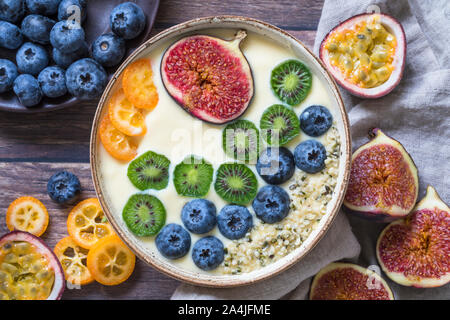 A fresh organic yogurt smoothie bowl seen from above with a variation of fresh fruits - blueberries, mini kiwis, figs, passion fruit and kumquat. Some - Stock Photo