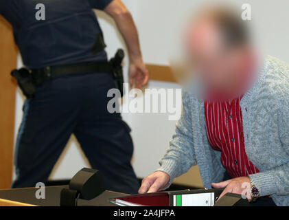Augsburg, Germany. 15th Oct, 2019. A defendant takes his seat in a courtroom of the Criminal Justice Center. The farmer from Northern Swabia has been standing before the Augsburg Regional Court since Tuesday because he is said to have knocked his wife unconscious and then poured liquid manure over her until she suffocated. The man denies the crime. Credit: Karl-Josef Hildenbrand/dpa - ATTENTION: The accused was made unrecognizable on personal rights grounds/dpa/Alamy Live News - Stock Photo